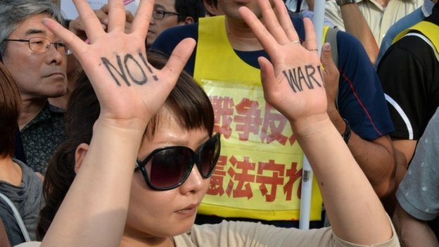 "A protester shows ""No War"" sign on her palms during a rally in front of the prime minister""s official residence in Tokyo on July 1, 2014."