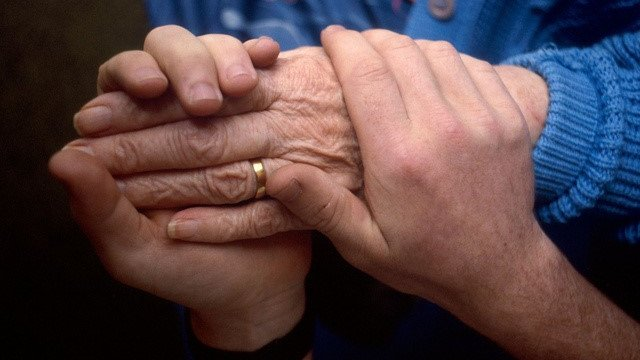 Person holding elderly woman's hand