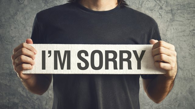 "Man holding ""I'm sorry"" sign"