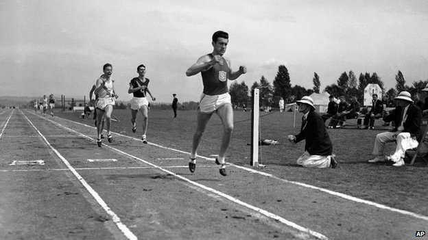 Louis Zamperini of he University of Southern California, breaks the tape and record with a time of 4:16.3 to win the mile run in the Pacific Coast Conference Track and Field meet the University of Washington Stadium in Seattle 20 May 1939