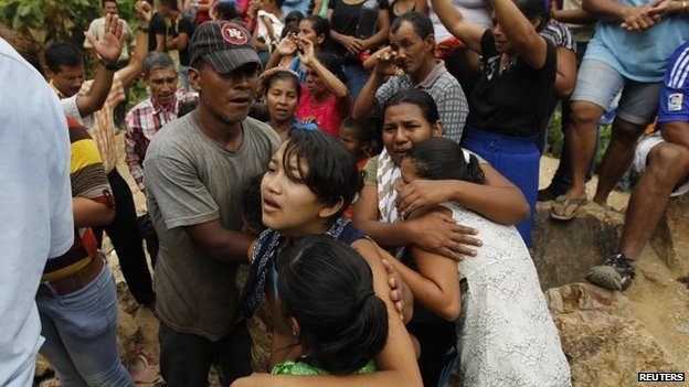 Relatives of trapped miners at the site of a landslide at a gold mine in San Juan Arriba, on July 3, 2014