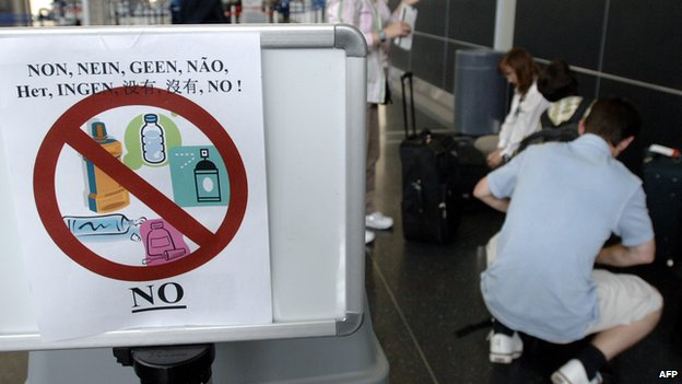 A group of travellers repack their baggage just before entering the security checkpoint to comply with new US air travel regulations prohibiting liquids in carry-on luggage, 10 August, 2006