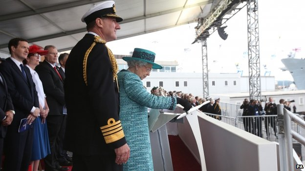 Queen Elizabeth II pressing the button to release the bottle of whisky at Rosyth Dockyard, Fife to formally name the Royal Navy's biggest ever ship, HMS Queen Elizabeth