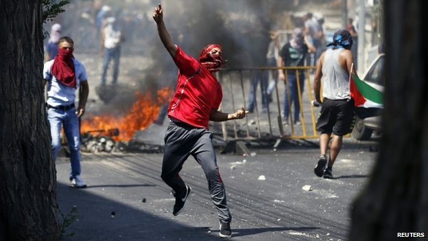 A Palestinian throws a stone during clashes with Israeli police after prayers on the first Friday of the holy month of Ramadan in the East Jerusalem neighbourhood of Wadi al-Joz July 4, 2014