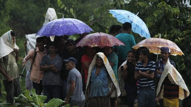 Miners and relatives take cover from the rain outside the mine. 04/07/2014
