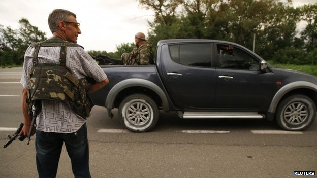 An armed pro-Russian rebel stands on the road as others drive past near the eastern Ukrainian city of Donetsk July 5