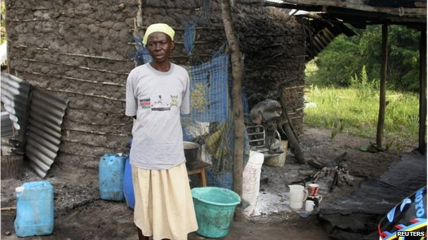 Woman stands next to burned house in Hindi, Kenya (6 July 2014)