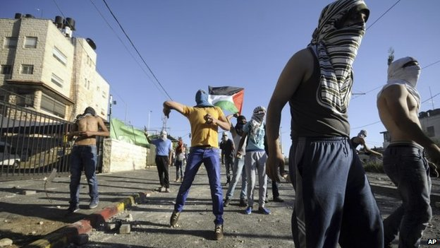 Palestinians throw stones during clashes with Israeli security forces in Jerusalem, July 3