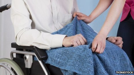 Carer and person in wheelchair