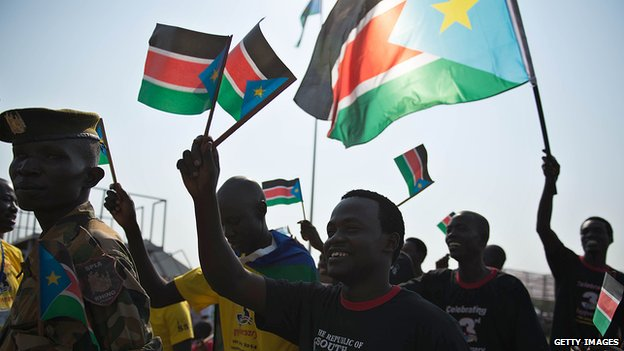 People waving South Sudanese flags
