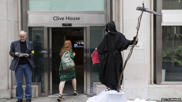 A man dressed as the Grim Reaper stands on a union picket line