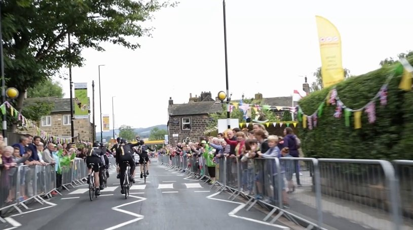 cyclists on the first stage of the Tour de France ride past cheering crowds