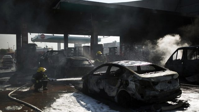 Israeli firefighters extinguish a fire that broke out after a rocket hit a petrol station in the southern city of Ashdod July 11, 2014