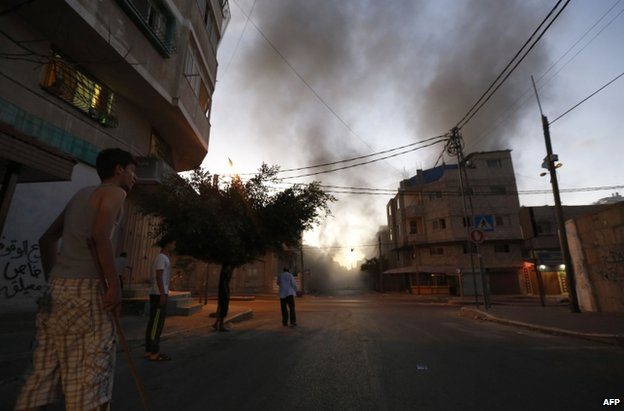 Palestinians watch smoke billowing after an Israeli air strike in Gaza City, 13 July