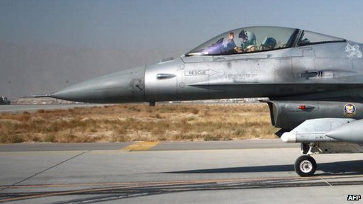 A pilot waves from the cockpit of a US F-16 fighter jet at Bagram air base, Afghanistan (2009)