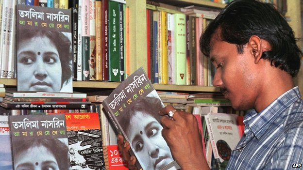A man looks through the latest book by Bangladeshi writer Taslima Nasreen (pictured on book) Aamaar meye belaa ('My Childhood Days') on 13 August 1999 in Calcutta.