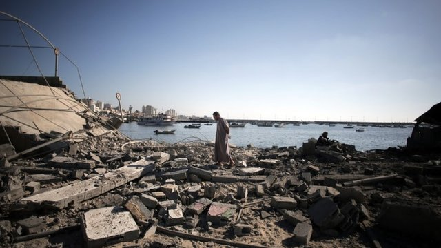 A Palestinian man inspects the damage of a police post, following an Israeli missile strike killing four boys from the same extended Bakr family, in Gaza City, Wednesday, July 16, 2014. The four boys, who were cousins and ages 9 to 11, were killed while playing on a beach off a coastal road west of Gaza City