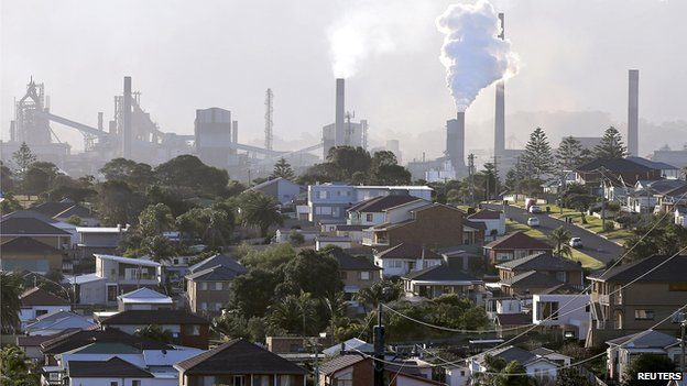 In this Wednesday, July 2, 2014 photo, smoke billows out of a chiming chimney stack of a steel works factories in Port Kembla 86 kilometers (53 miles) south of Sydney