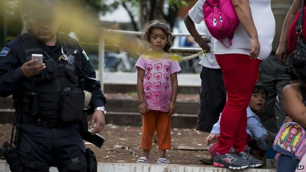A girl standing amongst relatives waiting to be reunited with their children inside a police cordon outside The Great Family home, in Zamora, Michoacan State, Mexico