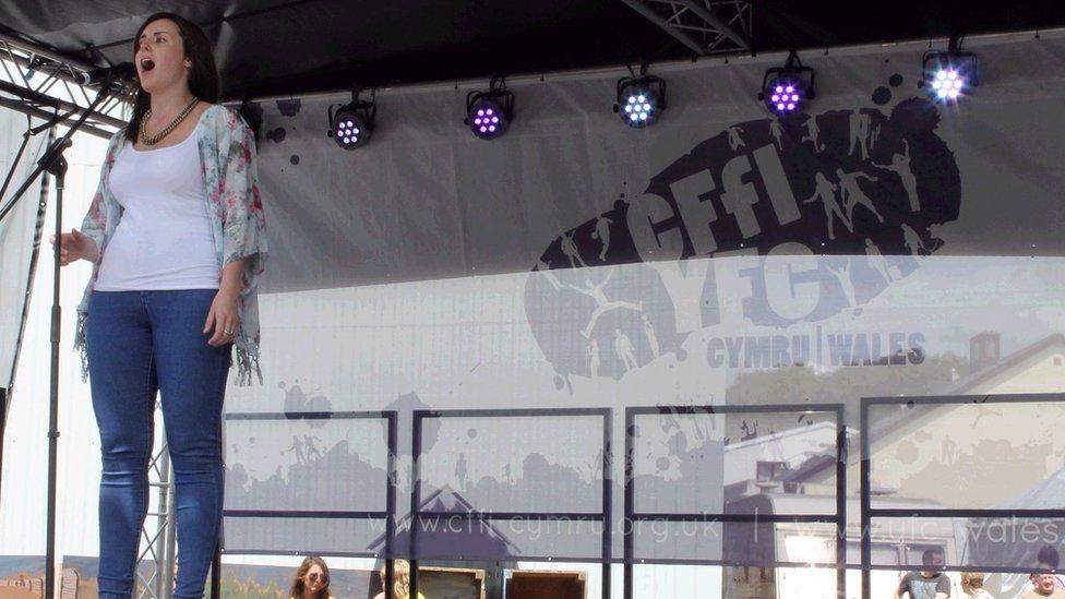 Catrin Reynolds o Geredigion yn cystadlu yng nghystadleuaeth Y Llais ar lwyfan y Ffermwyr Ifanc. >> Catrin Reynolds from Ceredigion made quite an impression whilst competing in The Voice competition on the YFC stage.