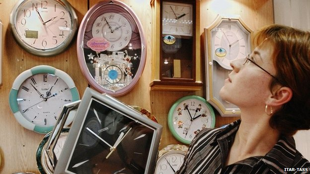 A woman looks at clocks of the Russian time zones