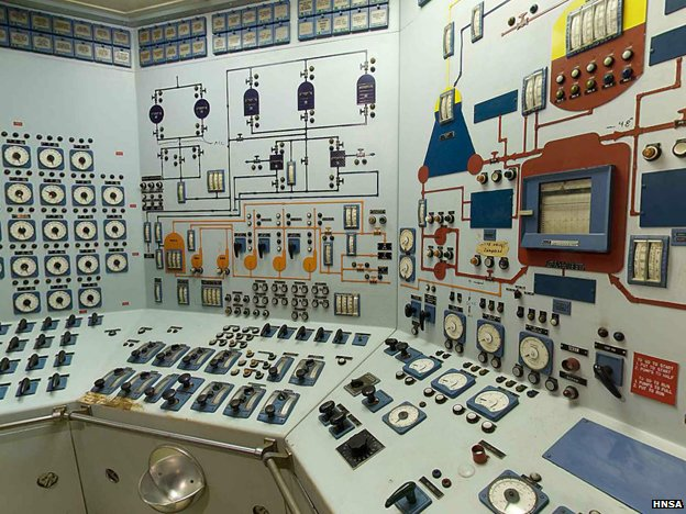 Control room covered in lights, gauges, switches and circuit illustrations