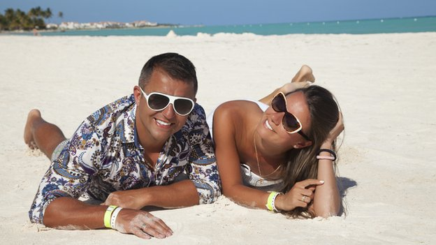 A man and a woman, both wearing sunglasses, lie on a sandy beach looking at the camera. The sea is in the distance behind them.