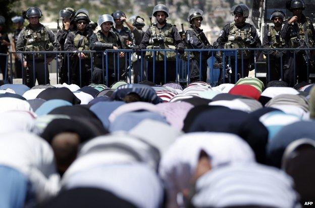 Israeli police watch Palestinians praying in East Jerusalem, 25 July