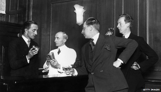 November 1927: Writers and brothers Osbert (1892 - 1969) and Sacheverell Sitwell (1897 - 1988) watch Martyn Roland of the Savoy Hotel and Harry Craddock the barman demonstrate how to shake a cocktail