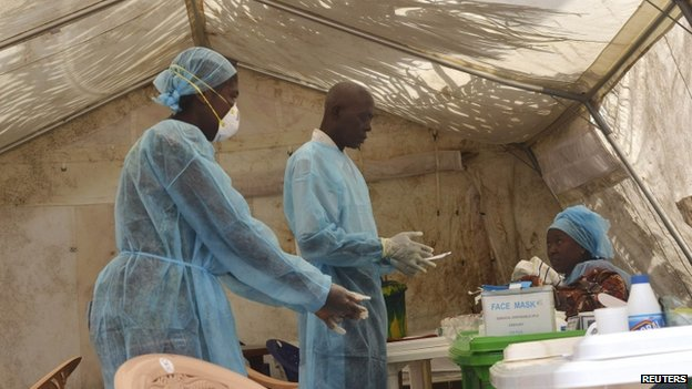 Health workers take blood samples for Ebola virus testing at a screening tent in the local government hospital in Kenema, Sierra Leone, on 30 June 2014.