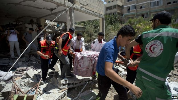 A body buried under rubble in Gaza is removed 27 July 2014