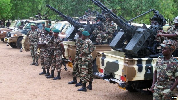 Cameroonian soldiers standing next to pick up trucks with mounted heavy artillery in Mora, northern Cameroon, on 17 June 2014