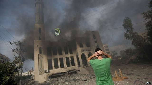 A man stands before a ruined mosque in Gaza City, 29 July