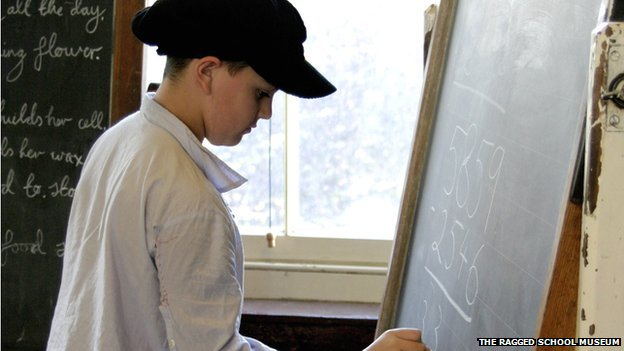 A schoolboy in Victorian clothes at a blackboard