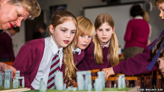 Children in a classroom look at a replica of Stonehenge