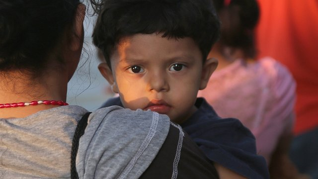 A Central American boy at the US-Mexico border is held in the arms of a woman.
