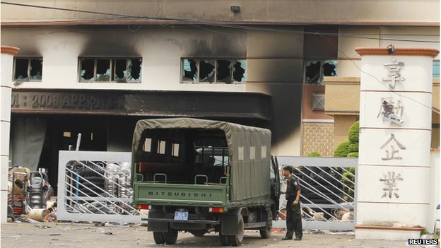 A riot police officer stands guard outside the damaged Shining company building in Vietnam's southern Binh Duong province on 16 May 2014
