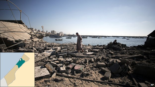 A Palestinian man inspects the damage of a police post, following an Israeli missile strike killing four boys from the same extended Bakr family, in Gaza City, Wednesday, July 16, 2014