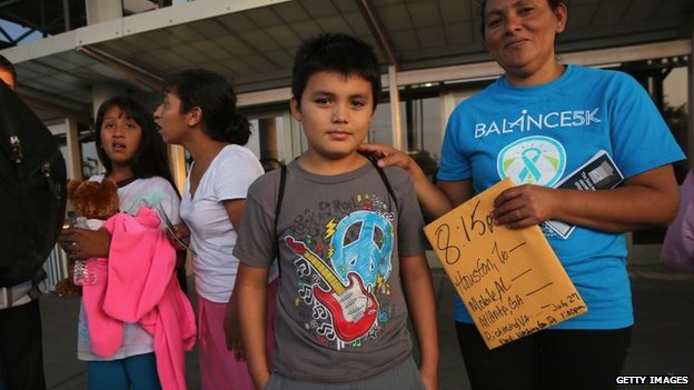 A Salvadorian family waits at a bus station after being released from immigration detention