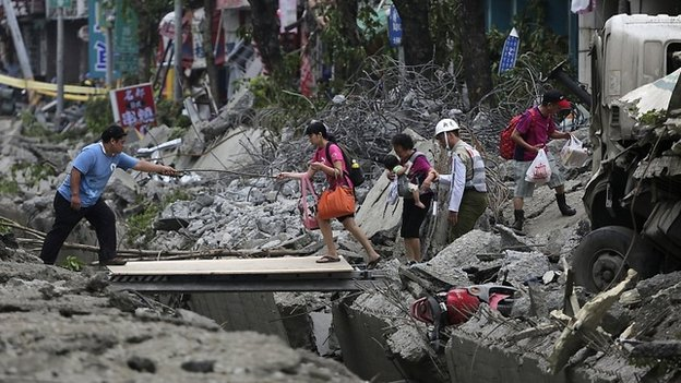People walk across a gap caused by an explosion in Kaohsiung - 1 August 2014