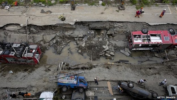 Damaged vehicles lie on the road after gas explosions in Kaohsiung - 1 August 2014