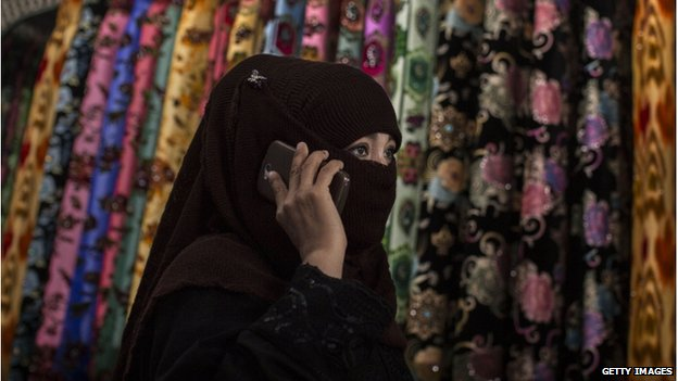 An Uighur woman wears a veil as she shops at a local market on 2 August 2014 in Kashgar, Xinjiang Province, China.