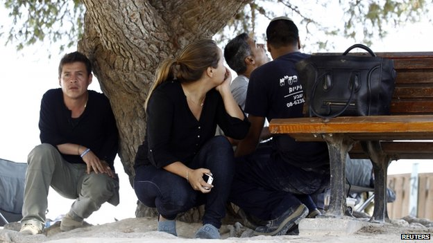 Israeli journalists and civilians seek cover during an air raid attack on the Gazan border (8 July 2014)