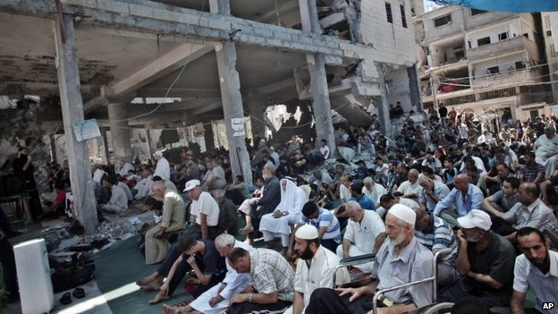 People attend Friday prayers at the site of a mosque that was bombed in Gaza (8 August 2014)