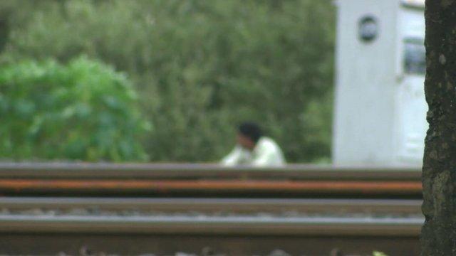 Man squatting next to a railway