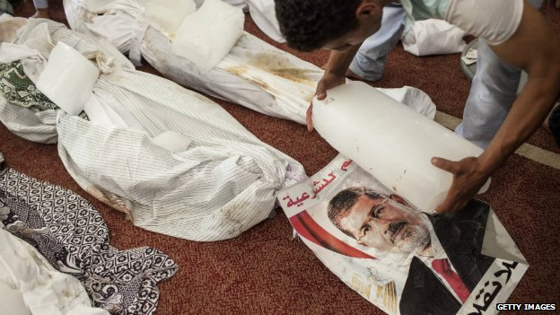 An Egyptian places blocks of ice next to the bodies of victims from the police offensive on the Rabaa protest camp in Cairo - 14 August 2014