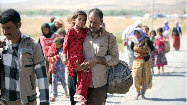 A displaced Iraqi man from the Yazidi community carries his daughter as they cross the Iraqi-Syrian border (11/08/2014)