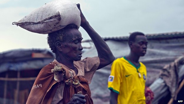 Elderly South Sudanese woman carries rice back to her refugee camp