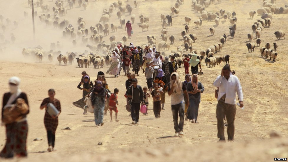 Displaced people from the minority Yazidi sect, fleeing violence from forces loyal to the Islamic State in Sinjar town, walk towards the Syrian border, on the outskirts of Sinjar mountain, near the Syrian border town of Elierbeh of Al-Hasakah Governorate.