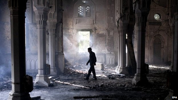 A man walks through Rabaa al-Adawia mosque the day after Egyptian security forces removed the protesters - 15 August 2013